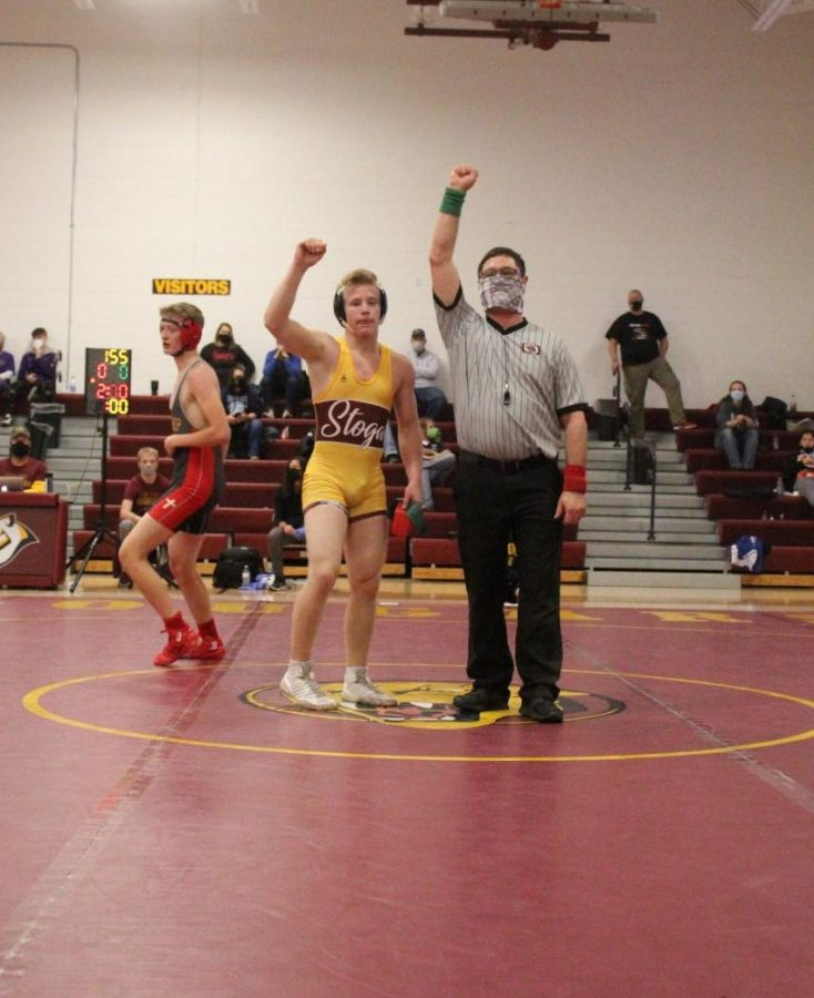 Carter Plowman's hand is raised in victory following his championship finals match. Plowman (145) and Keaghon Chini (126) led the way for Conestoga with first place finishes.