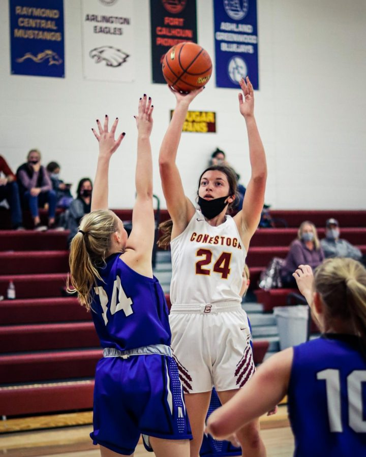 Sophia Ackerman (24) shoots over a Malcolm defender in this Dec. 2020 matchup. The school's basketball teams have been playing in front of smaller than usual crowds this season.