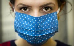 A woman wears a cloth mask to help prevent the spread of the novel coronavirus. Infection rates are down, but we must continue taking precautions until the virus no longer poses a major threat to our population.