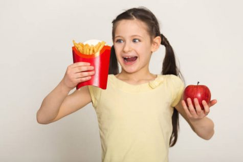 Happy little girl holding a bag of fries and apple isolated on white background. Fast food against healthy food concept, copy space