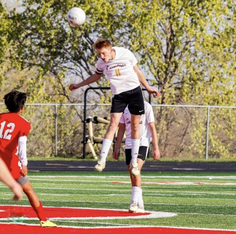 Defender Koby Vogler soars through the air as he heads a ball against Platteview.
