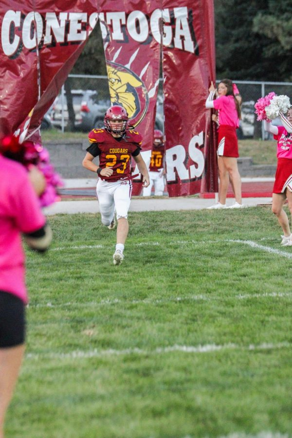 Keaghon C. takes the field while the cheerleaders cheer the team on.